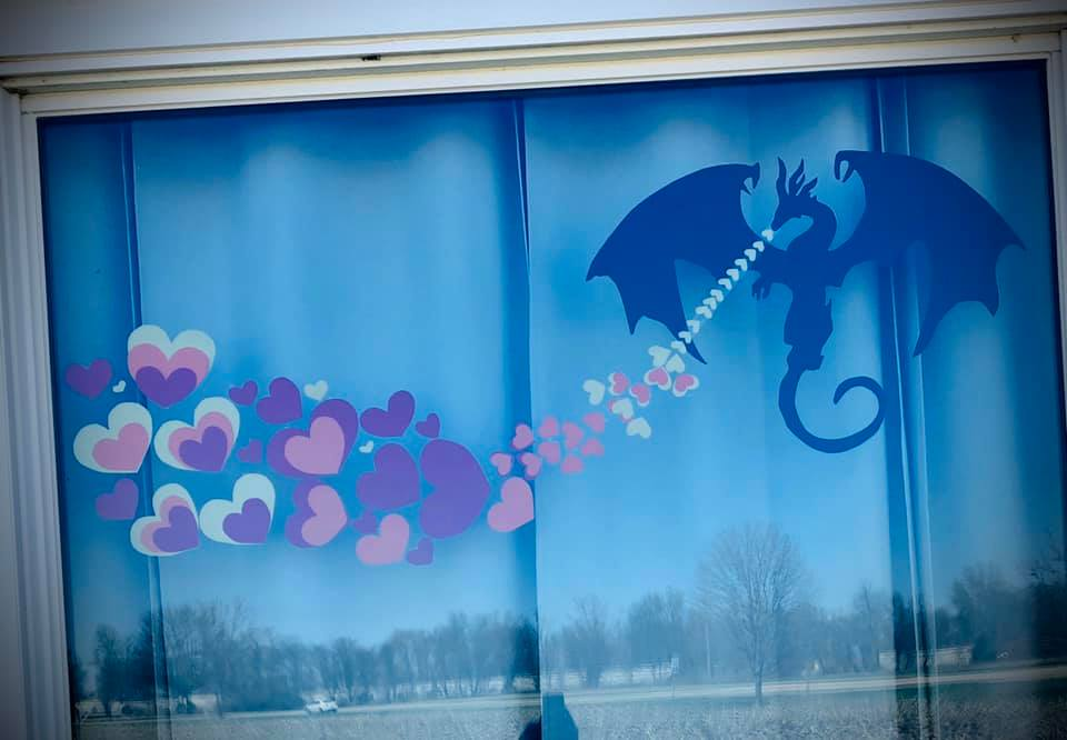 in window: Paper dragon breathing paper hearts