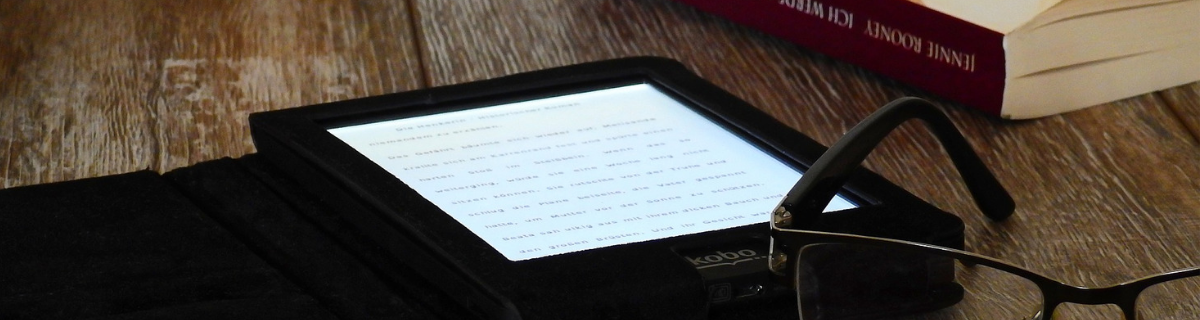 image: e-reader, paperback book, and reading glasses on brown wooden table