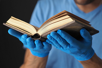 person in medical scrubs and wearing medical gloves holding an open book